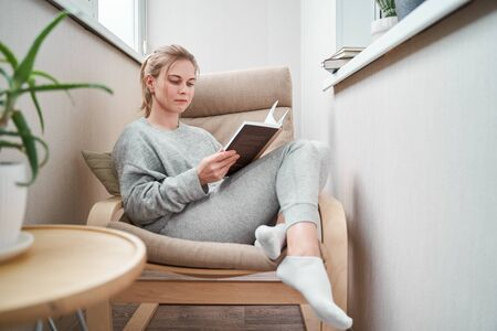 Young girl reading book while sitting on beige armchair in apartment