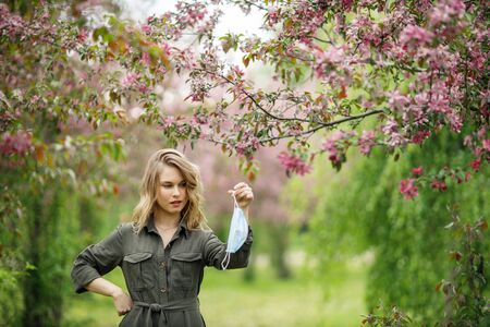 Blonde woman in medical mask on background of flowering trees in park at afternoon.