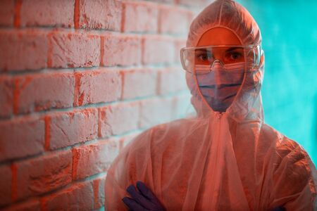 Young doctor in protective suit on background of brick wall.