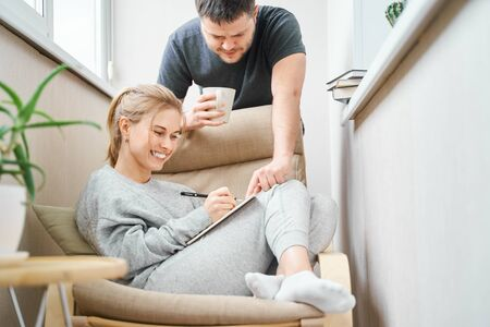 Smiling blonde woman sitting on beige armchair and brunet man standing beside her on balcony Banco de Imagens