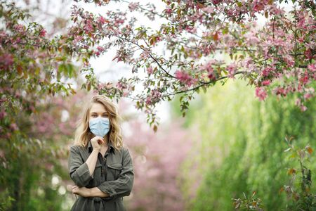 Young blonde in medical mask on background of flowering trees in park . Banco de Imagens