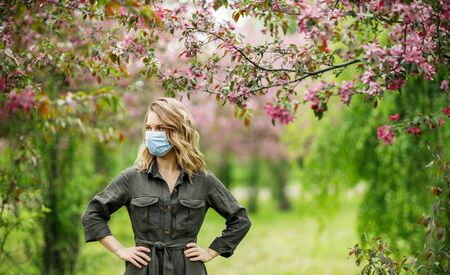 Blonde woman in medical mask on background of flowering trees in park.