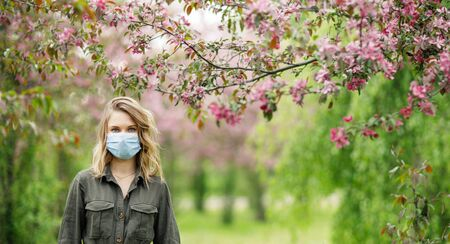Young woman in medical mask on background of flowering trees in park