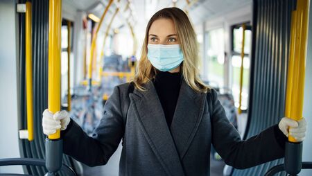 Blonde woman in medical mask looking at camera while standing in bus lounge.