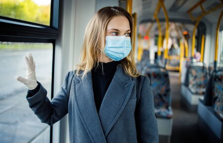 Blonde in medical mask and protective gloves standing by window in bus.