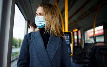 Young blonde woman in medical mask standing at window in bus.