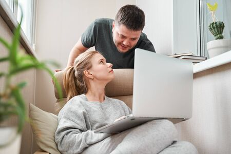 Woman sitting on beige armchair with laptop and man in apartment