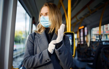 Young blonde in medical mask and protective gloves standing by window in bus.
