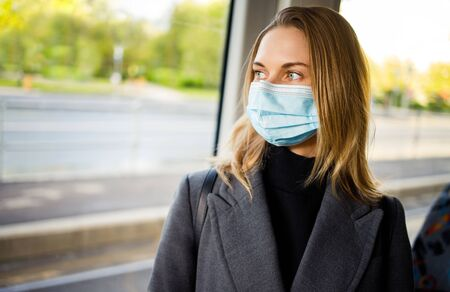 Blonde in medical mask standing at window in bus.