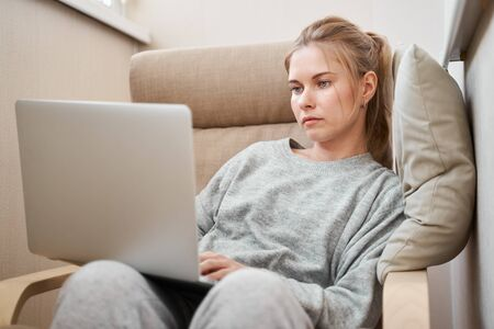 Serious woman in gray home suit with laptop in her hands