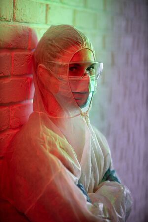 Young doctor in protective suit on background of brick wall in red zone.
