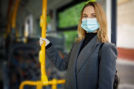 Blonde in medical mask holding handrail while standing in bus lounge.