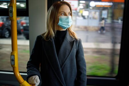 Young blonde in medical mask holding handrail while standing in bus lounge.