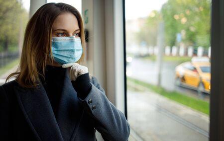 Pensive woman in medical mask standing at window in bus. Banco de Imagens