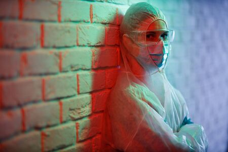 Young nurse in protective suit on background of brick wall in red zone.