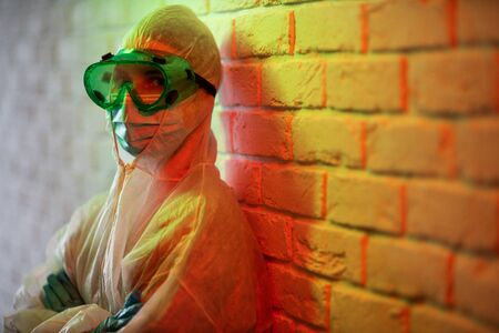 Young doctor in protective suit and glasses on background of brick wall in red zone Banco de Imagens