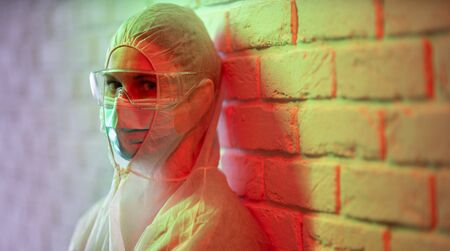 Doctor in protective suit on background of brick wall in red zone. Banco de Imagens