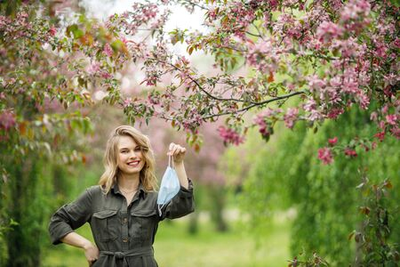 Young blonde in medical mask on background of flowering trees in park at afternoon.