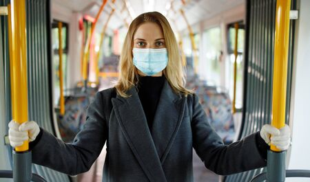 Blonde in medical mask looking at camera while standing in bus lounge.