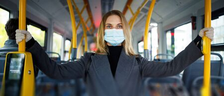 Young blonde in medical mask looking at camera while holding handrail while standing in bus lounge.