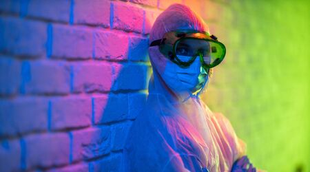 Young doctor in protective suit and glasses on brick wall background. Banco de Imagens