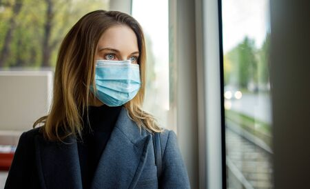 Blonde woman in medical mask standing at window in bus.