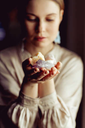 Young european girl holding a gemstone with boths hands in front of her. Mystical woman. Occult, witchcraft scene. Close up paranormal portrait.