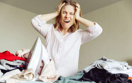 angry young girl ironing clothes at home