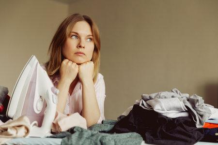 Sad young woman ironing clothing at home