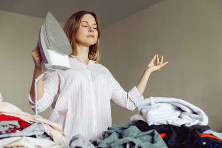 Young girl meditates before ironing clothes at home 免版税图像
