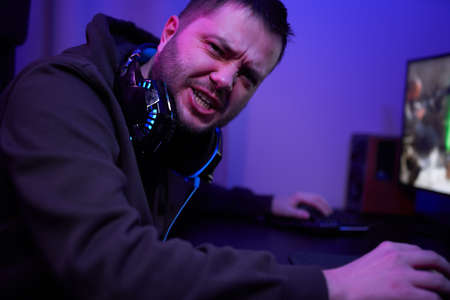 Gamer or streamer in headphones with microphone sits at home in neon light and plays at pc 免版税图像