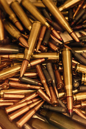 Pile of bullets with copper tips under a warm light. Close up of a lot of bullets. Gun violence in America. Ammunition rifle or pistol. toned