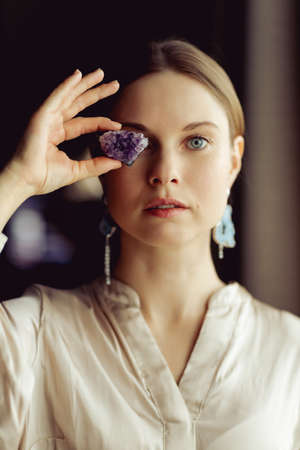 Young european girl holding a gemstone in hand in front of her. Looking towards the camera. Mystical woman..