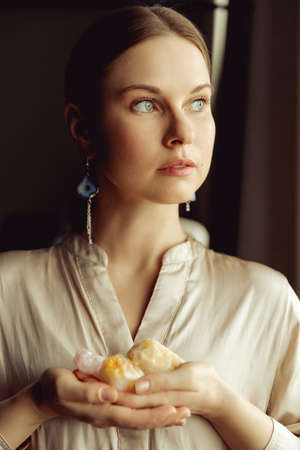Young european girl holding a gemstone with boths hands in front of her. Looking towards the camera. Mystical woman. Occult, witchcraft scene. 免版税图像