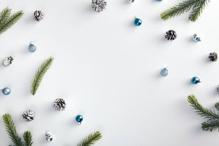 Christmas minimal concept - blue christmas baubles, fir branch and cones on white background. Christmas decoration top view for celebration design. Minimal flatlay. Holiday frame.