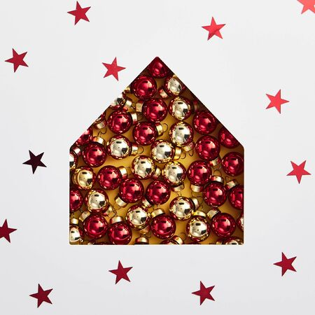 Christmas minimal concept - christmas house silhouette made of bauble with star confetti. Flat lat, top view. Square composition. Country cottage concept. House abstract real estate.