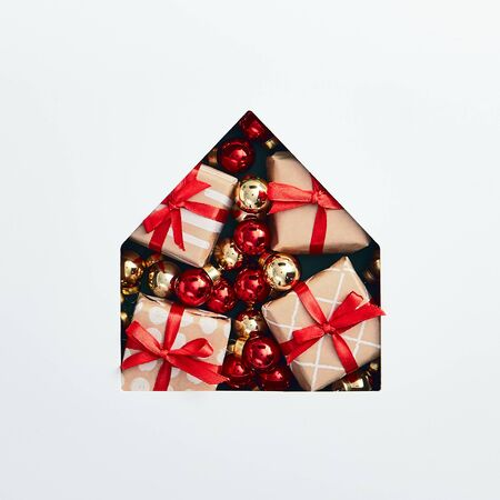 Christmas minimal concept - christmas house silhouette made of bauble and xmas gifts. Flat lat, top view. Square composition. Minimal concept. Christmas gift box.