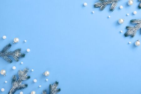 Christmas minimal concept - Christmas composition with snowy fir branch and white bauble. Horizontal corner composition, flat lay, view from above. Classic blue background with copy space