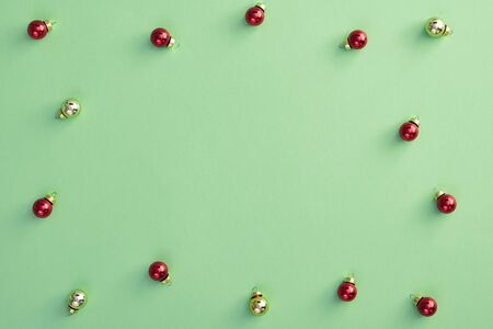 Christmas minimal concept - pattern with christmas balls on pastel green background. Xmas background with copy space, design for any purposes. Christmas ball for wallpaper design.  Stock Photo