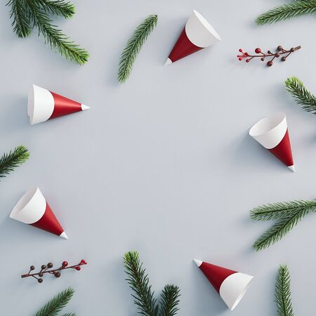 Christmas minimal concept - christmas composition with party cone, red berry and evergreen tree on pastel color background. Copy space, flatlay. Celebrate concept. Holiday background. Blue background. Stock Photo