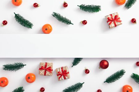 Christmas minimal concept - Christmas composition made of tree branch, gift box, bauble and tangerine on white background. White paper blank for text space. Christmas, winter concept. Winter season.