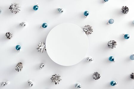 Christmas minimal concept - blue christmas baubles and cones on white background. White round paper frame. Xmas holiday. Christmas decoration. Christmas holiday composition. Round frame composition.