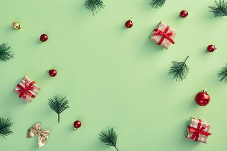 Christmas minimal concept - pattern with christmas balls, golden bow, xmas gift box and pine branch on pastel green background. Copy space, design for any purposes. New year present concept. Stock Photo