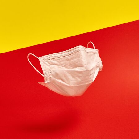 Surgical face mask on red and yellow background. Minimal medical concept. Medical equipment