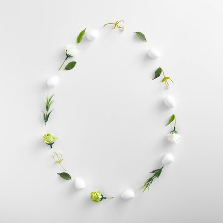 Spring herbs and flowers oval shaped composition on white background. Blooming buds and fresh green leaves, grass and foliage close up. Easter holiday rustic style decoration with botanical elements.