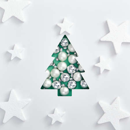 Christmas minimal concept - Trendy aqua menthe xmas tree made of white and silver bauble. Square composition, flat lay, view from above. Abstract white star pattern