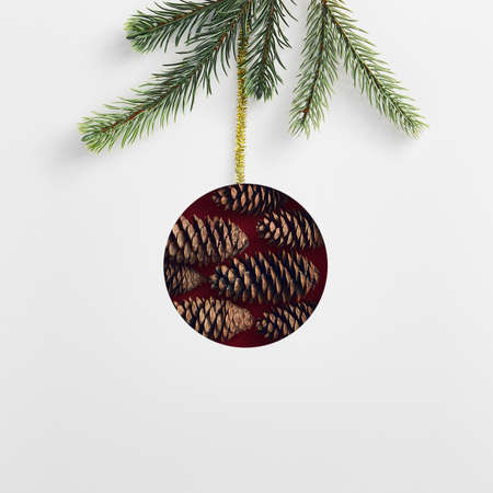 Christmas minimal concept - abstract christmas bauble made of pinecone. Evergreen tree branch. Shape bauble christmas minimal in abstract style on white background. Winter holiday decoration.