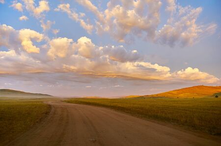 unusually: Clouds unusually highlighted by rising sun over dirt road