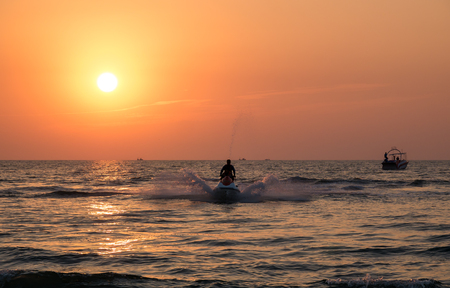 A strong man drive on the jet ski above the water at sunset .silhouette. spray. Stock Photo