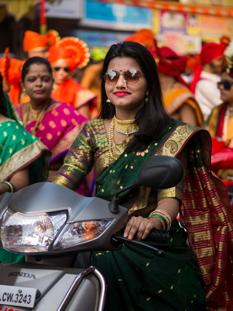 Mumbai, India - MARCH 18, 2018 : A beautiful indian female dressed in traditional attire driving a bike during a procession celebrating Gudhi Padwa or the Maharashtrian new year in Mumbai Editorial